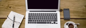 Apple MacBook with notepad and cup of coffee on wooden desk